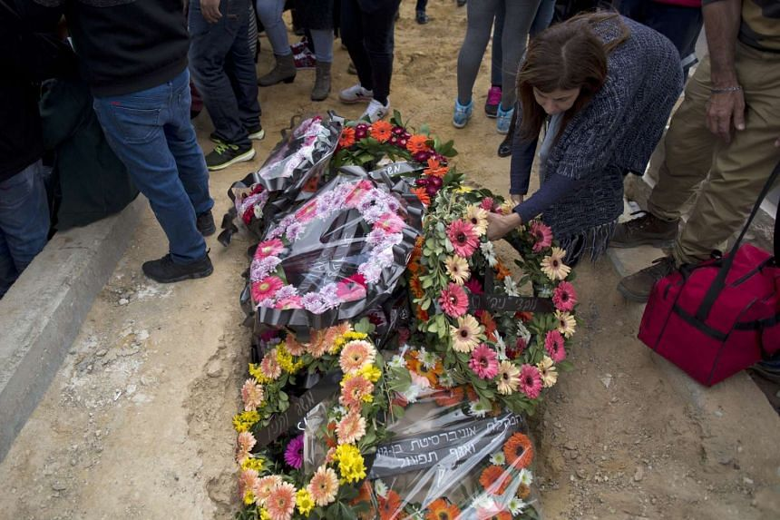 A relative lays a wreath on Simcha Damari's grave, one of the Israeli victims of the Istanbul blast on March 19, at her funeral in the southern city of Dimona, Israel.