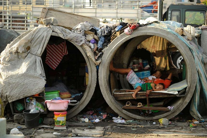 Families live in concrete pipes used as makeshift dwellings along a street in Manila.