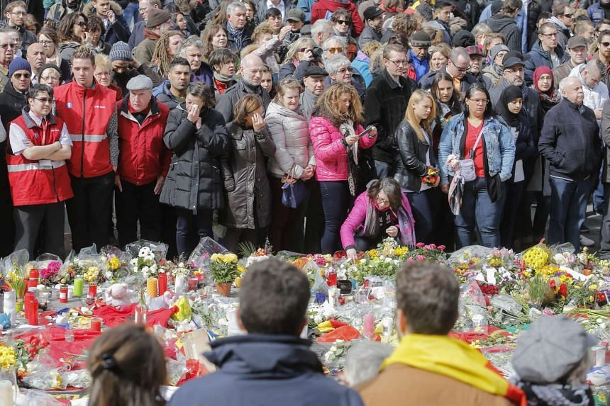 People gather to commemorate the victims of the March 22 terror attacks, at the site of a memorial in Place de la Bourse in Brussels, Belgium on March 27, 2016.