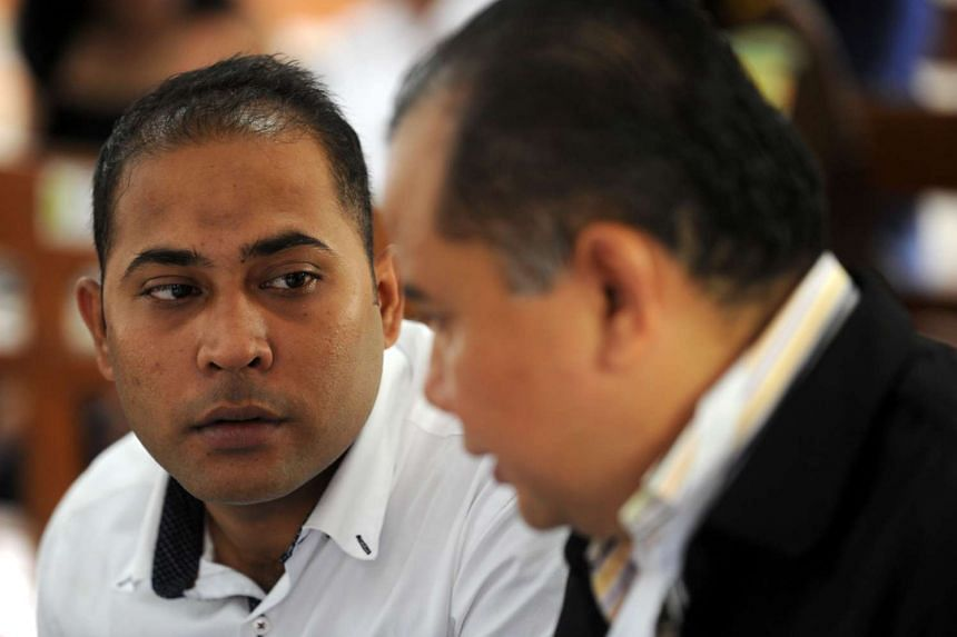 Sayed Mohammed Said (left) speaks with his lawyer in the courtroom before proceedings for his sentencing on drug-related charges in Denpasar begin.