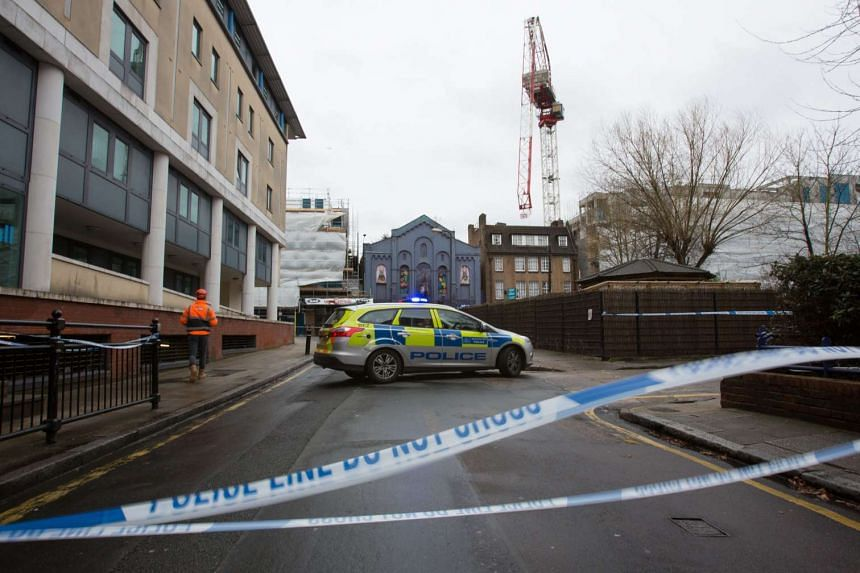 A police car parked in a closed area after a construction crane was bent overnight in high winds brought by Storm Katie in south London, on March 28, 2016.