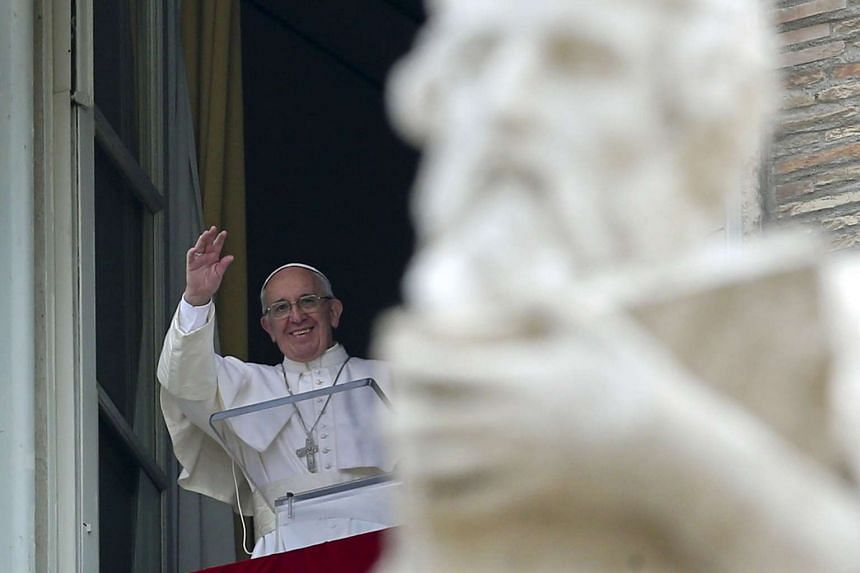 Pope Francis waves as he leads the Angelus prayer in Saint Peter's square at the Vatican, on March 28, 2016.