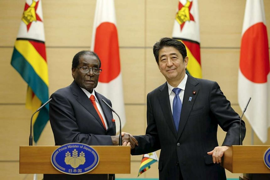 Shinzo Abe shakes hands with Robert Mugabe (left) after a press briefing on March 28, 2016.