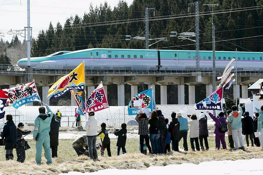 People waving flags as the first train of the new Hokkaido shinkansen, or bullet train, bound for Shin-Hakodate Hokuto Station from Tokyo, approached Kikonai Station in Kikouchi town on Japan's northern island of Hokkaido last Saturday. The long-awai
