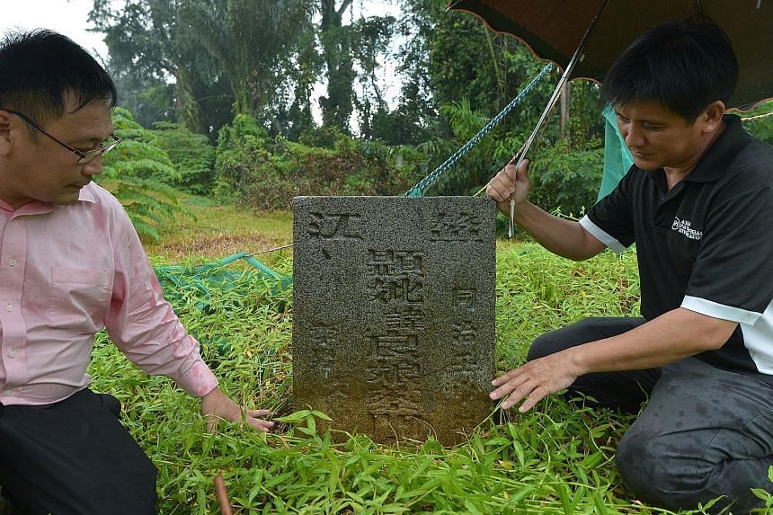 """A remnant of the boundary wall (right) of the 129-year-old former lunatic asylum and (far right) """"tomb- hunters"""" Raymond (in pink) and Charles Goh with one of the Chua family tombstones. The structures were found in late 2014."""
