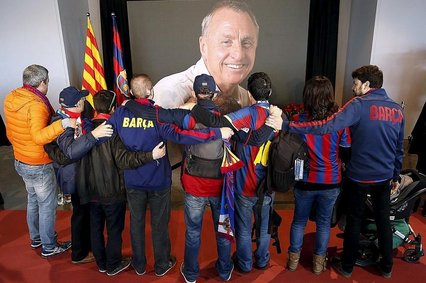 Supporters clad in Barcelona's colours embrace while paying tribute to Dutch legend Johan Cruyff, who won multiple honours with the Catalonian side as player and later, manager.