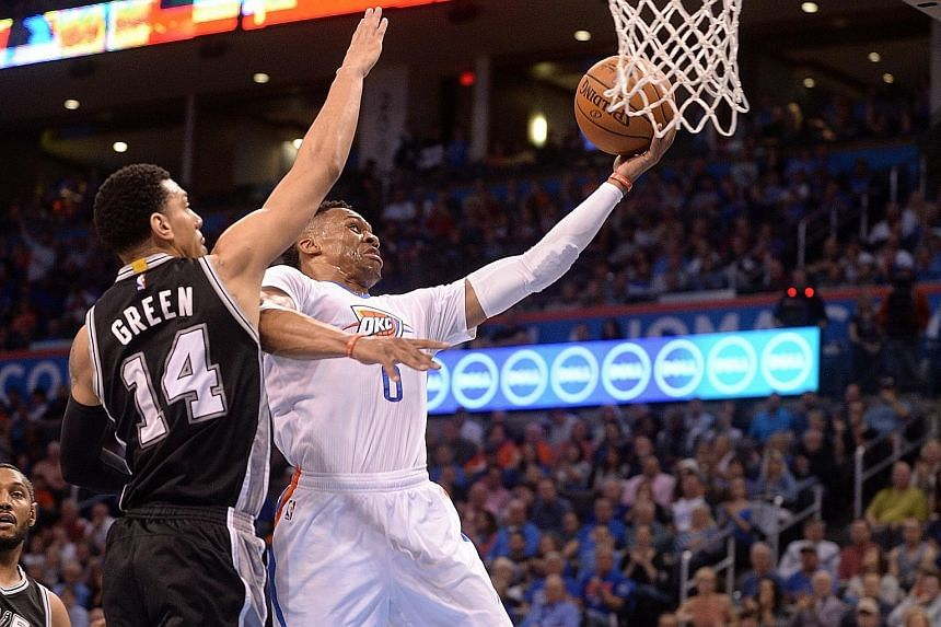 Oklahoma City guard Russell Westbrook driving to the basket in front of San Antonio guard Danny Green during their game at Chesapeake Energy Arena. The Thunder won easily 111-92 against the under-manned Spurs.