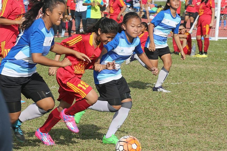 Team TPSS Titanides (in red) playing against Team Bullet Girls in a five-a-side tournament during Women's Football Day last month. About 550 women and girls took part in the event. Women's football here is poised for a revival after years in the dold