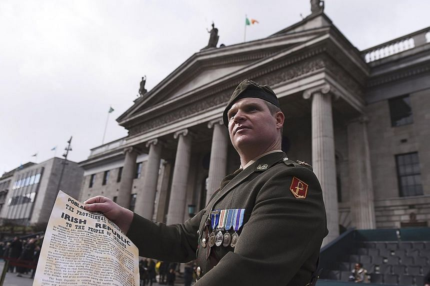 Commandant Pat O'Connor holding the Proclamation of the Republic outside the General Post Office, the rebels' headquarters, during the commemoration of the 100-year anniversary of the Easter Rising in Dublin, Ireland, yesterday.