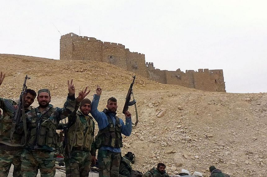 Syrian pro-government forces posing in victory near the ancient Palmyra citadel yesterday. The city is an important symbolic and strategic prize for President Bashar al-Assad's forces, as it provides control of the surrounding desert extending all th