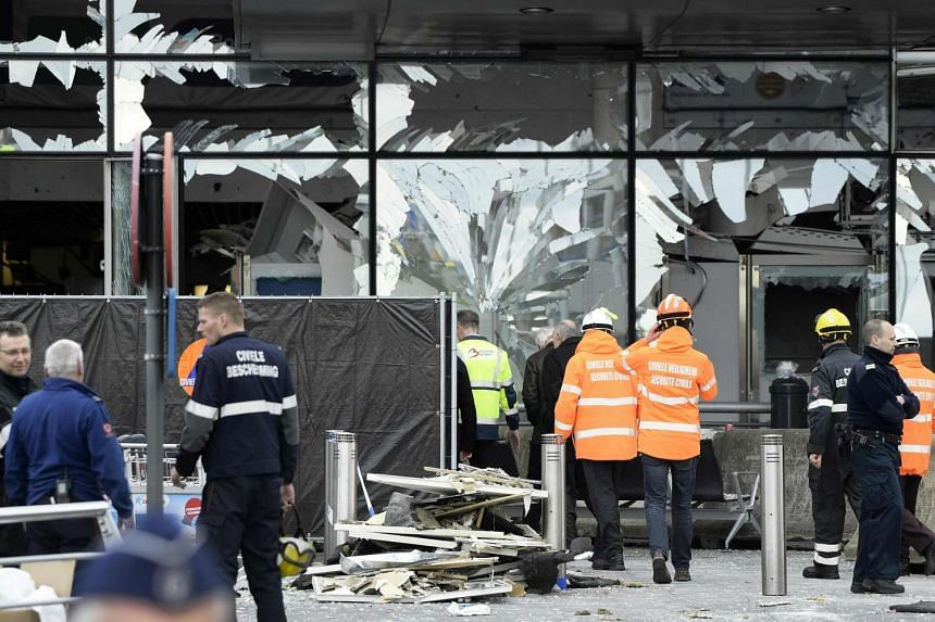Members of the civil protection walk outside the damaged front of Brussels Airport in Zaventem, on March 23, 2016.