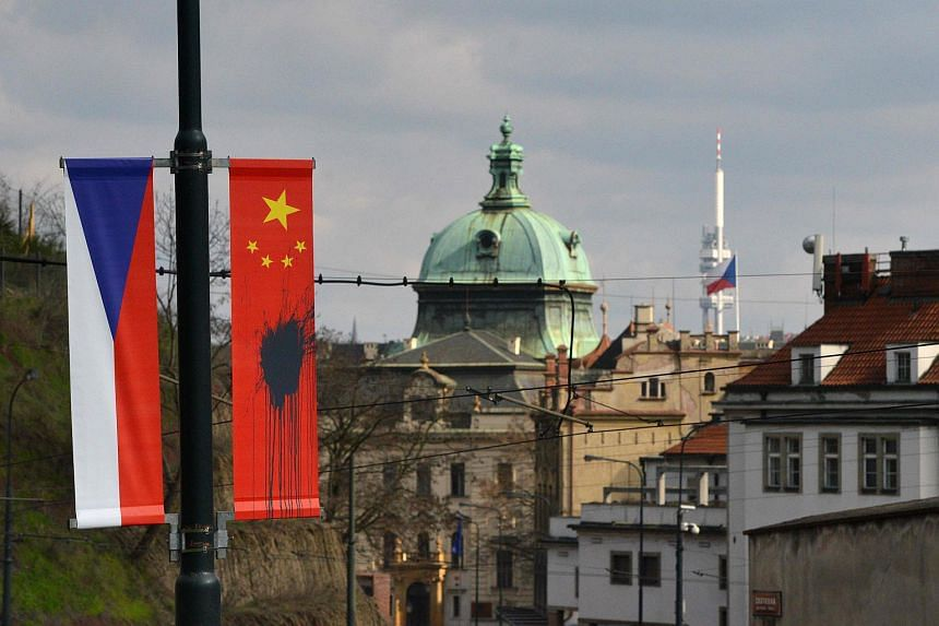 A Czech National flag hanging next to a Chinese National flag splattered with a black substance in Prague on March 26, 2016.
