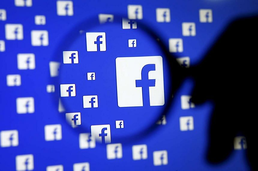 A man poses with a magnifier in front of a Facebook logo.