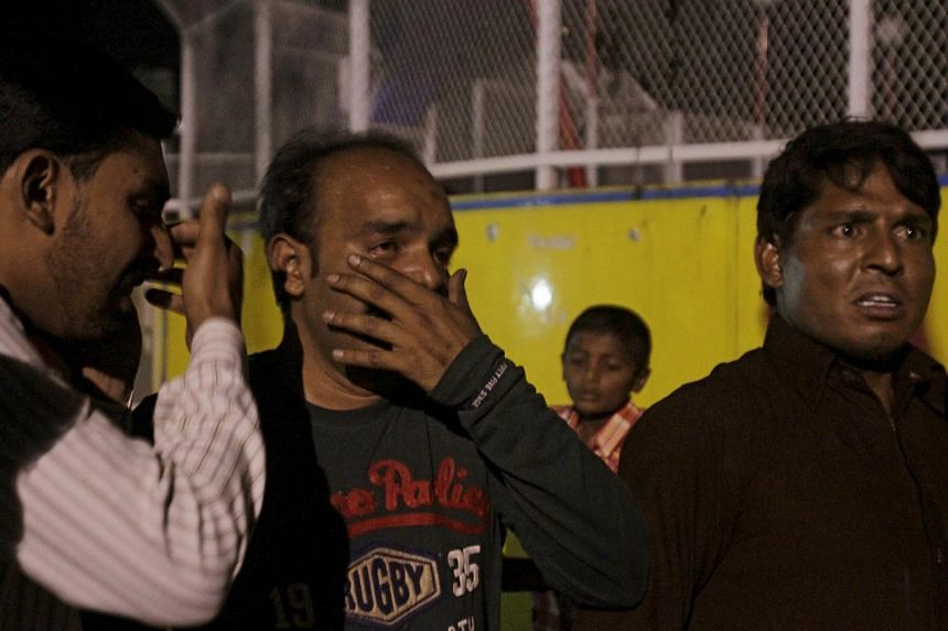 Men mourn the death of their relatives after a blast outside a public park in Lahore, Pakistan, on March 27, 2016.