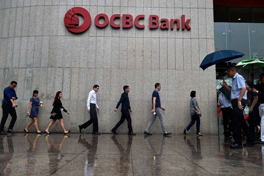 Office workers shelter themselves from the rain as they walk past the OCBC Centre at Raffles Place.