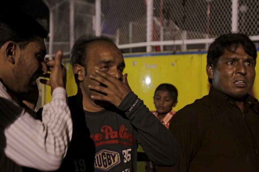 Men mourn the death of their relatives after a blast at a public park in Lahore, Pakistan on Easter Sunday (March 27).