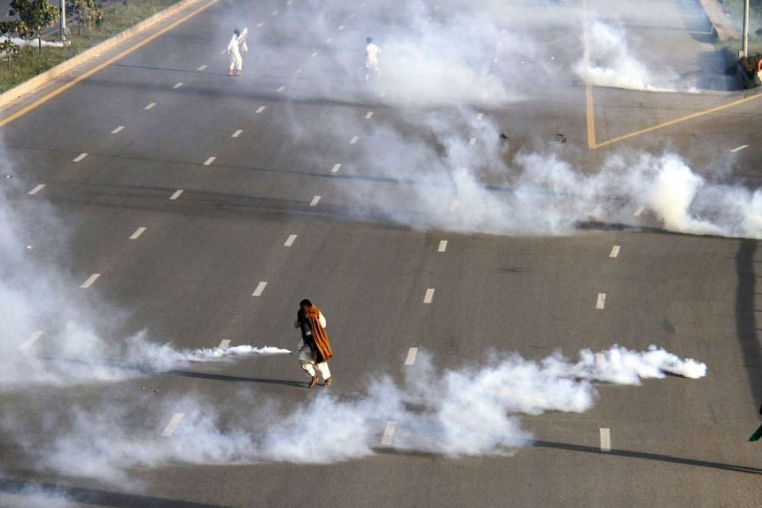 People run amid tear gas fired by policemen to disperse protesters who are marching towards the Parliament during a protest on the Chehlum (the fortieth day) of execution of Mumtaz Qadri, in Islamabad, Pakistan on Sunday (March 27).