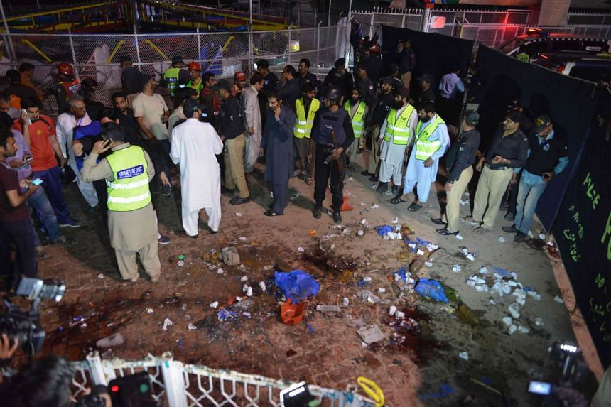 Pakistani rescuers and officials gather at the bomb blast site at the Lahore park on Sunday (March 27).