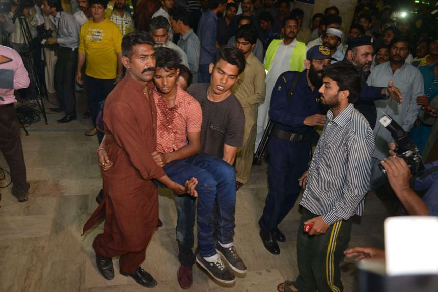 Pakistani relatives shift an injured bomb blast victim into a hospital after the bomb blast in Lahore on Easter Sunday (March 27).