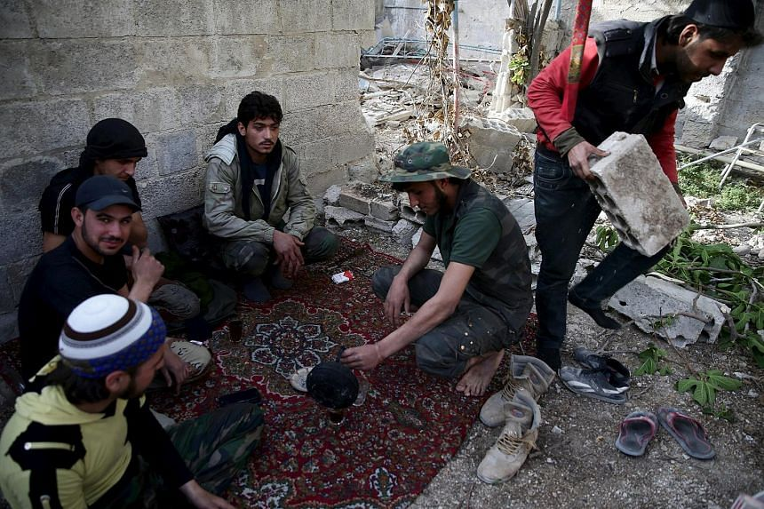 Free Syrian Army fighters rest in the rebel-controlled area of Jobar, a suburb of Damascus, Syria, on March 23, 2016.