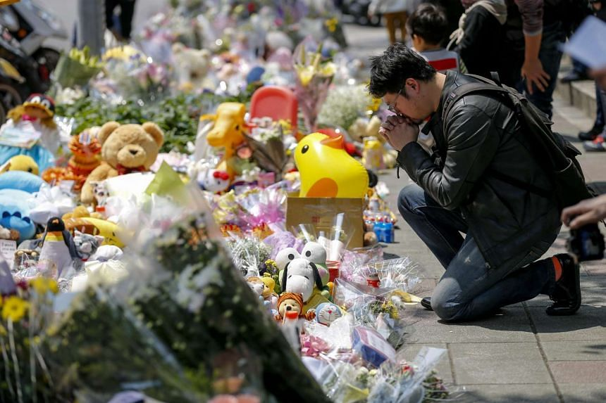A man offers flowers and prayers a four-year-old child victim of a random killing, at a makeshift memorial at a street next to the crime scene, in Taipei, Taiwan, on March 29, 2016.