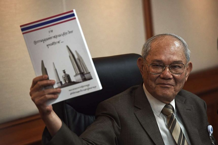 Constitution Draft Commission (CDC) chairman Meechai Ruchupan holds up Thailand's proposed new constitution at Parliament House in Bangkok on March 29, 2016.