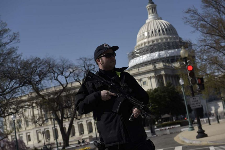 A police officer stands guard at the US Capitol complex in Washington, DC, on March 28, 2016 after reports of shots fired.
