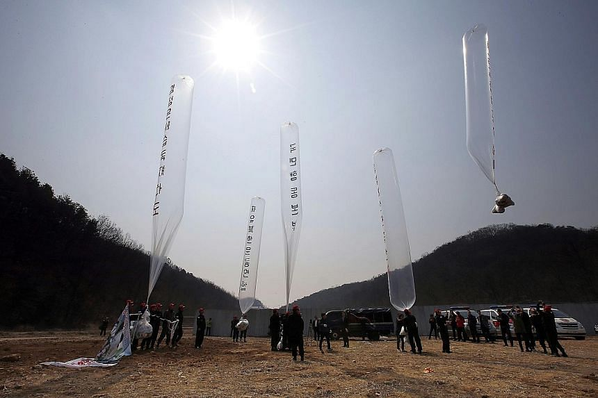 South Korean conservative activists launching large balloons carrying anti- Pyongyang leaflets at a field near the Demilitarised Zone dividing the two Koreas in Paju yesterday. The group sent the tens of thousands of leaflets criticising the North's