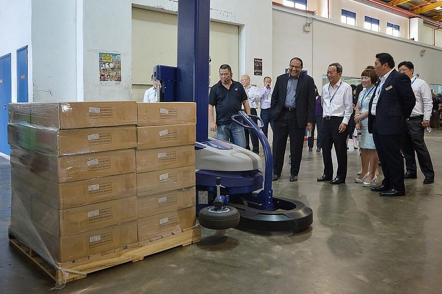 Mr Iswaran (second from left) observing a demonstration by Goodrich Global logistics manager Steven Tan (far left) of a pallet wrapping robot. Mr Iswaran was accompanied by (from right) WAF's vice-chairman Neo Kah Kiat, its council member Audrey Chin