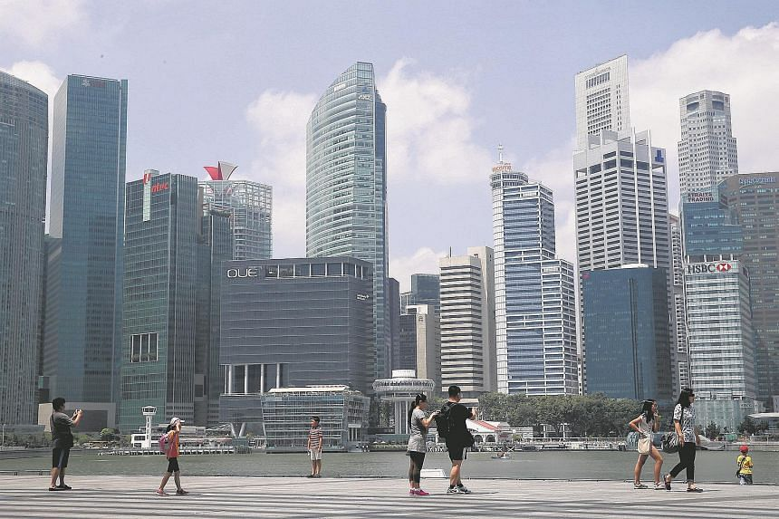 Tourists walking along the path on the waterfront promenade, along Marina Bay Sands against the skyline of the Central Business District.