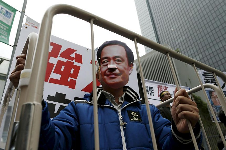 A demonstrator wears a mask depicting Causeway Bay Books shareholder Lee Bo during a protest over the disappearance of booksellers, in Hong Kong, on Jan 10, 2016.