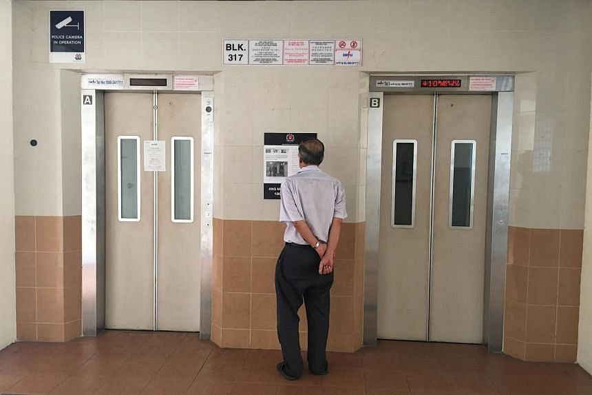 A man reads an article pasted at the lift lobby in Ang Mo Kio, where an Indonesian maid was trapped by a faulty lift (left) on March 7, 2016.