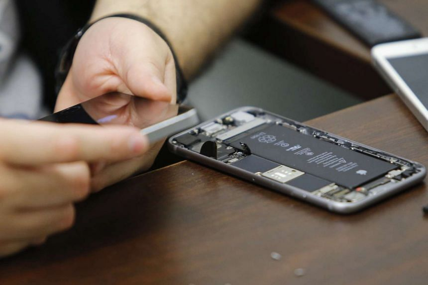 A worker checks an iPhone in a repair store in New York.