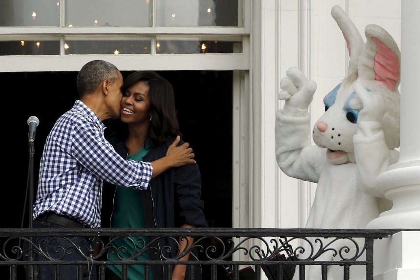 US President Barack Obama and first lady Michelle Obama share a kiss as they preside over the annual Easter Egg Roll at the White House in Washington on Monday (March 28).