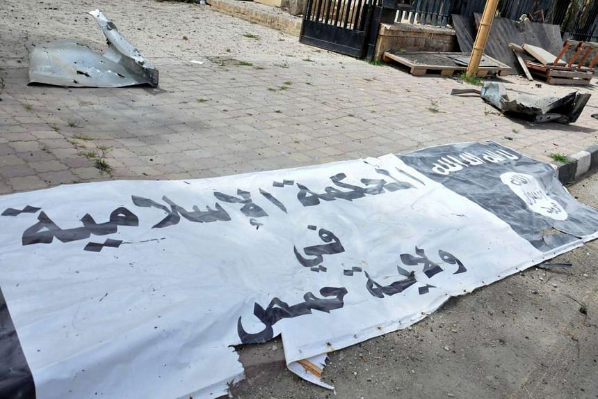 A banner belonging an ISIS court  is seen on the ground after Syrian forces recaptured Palmyra on Sunday (March 27)..