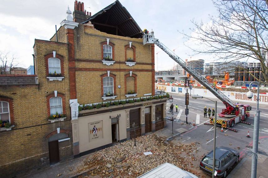 Members of the London fire brigade assess the damage at The Duchess public house after Storm Katie's high winds brought down part of the building's roof support  on Monday (March 28).