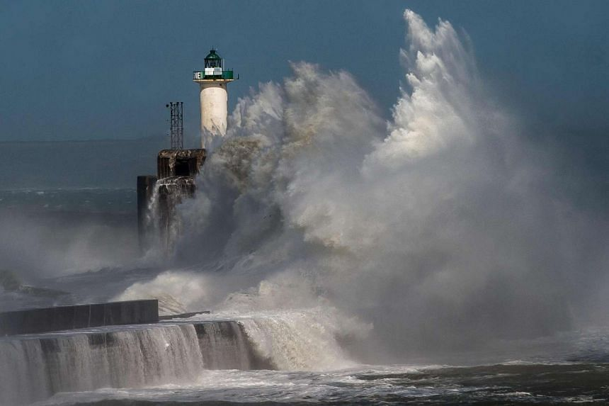 A wave breaks against a pier in front of a lighthouse in Boulogne-sur-Mer, France, on Monday (March 28).