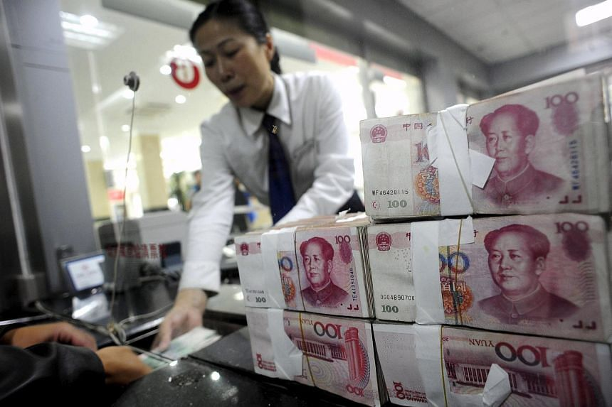 An employee hands Renminbi banknotes to a customer at a branch of the Industry and Commercial Bank of China.