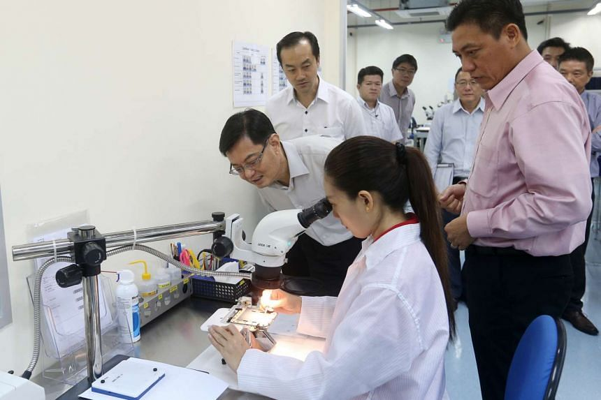 Mr Heng (left) with Minister of State for Trade and Industry Koh Poh Koon (behind Mr Heng) visiting precision engineering firm Feinmetall Singapore in Marsiling yesterday. During the visit, Mr Heng said that teams were being set up to develop road ma