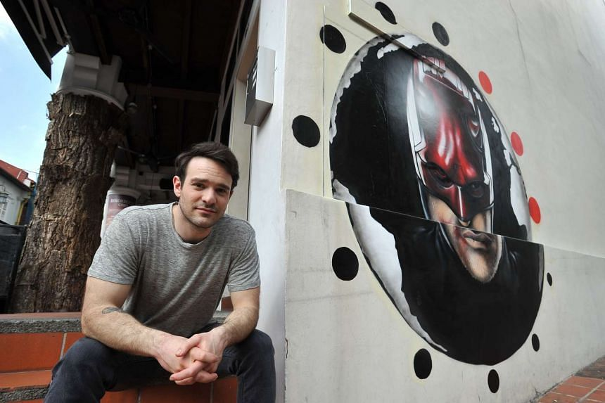 Charlie Cox poses next to a mural of his television character Daredevil on a wall in Club Street. The mural was created by British street artist Insa.