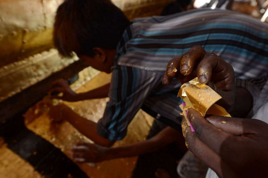 A Myanmar craftsman prepares a square gold leaf to cover the Sule Pagoda's tower, on March 12, 2016.