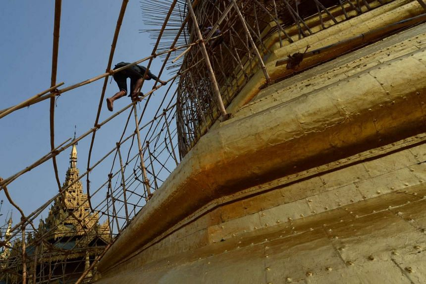 Myanmar craftsmen dismantle bamboo scaffolding on a section of the Sule Pagoda tower after installing gold covering, on March 12, 2016.