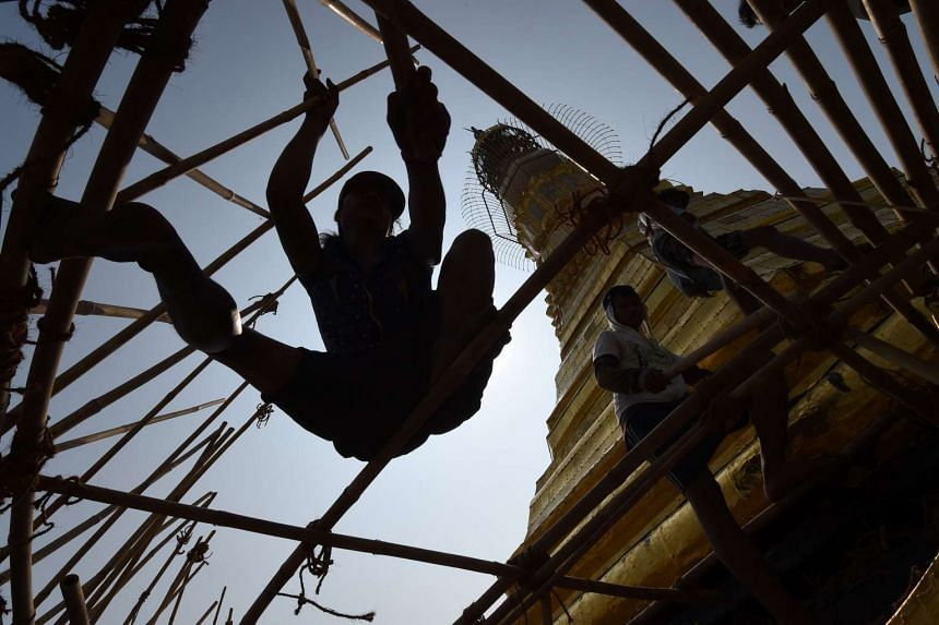 Myanmar craftsmen dismantle bamboo scaffolding on a section of the Sule Pagoda tower after installing gold covering, on March 14, 2016.