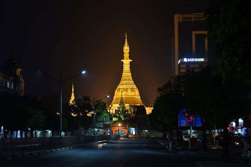 Sule Pagoda tower, newly covered with gold, glows under spotlights before dawn, on March 23, 2016.
