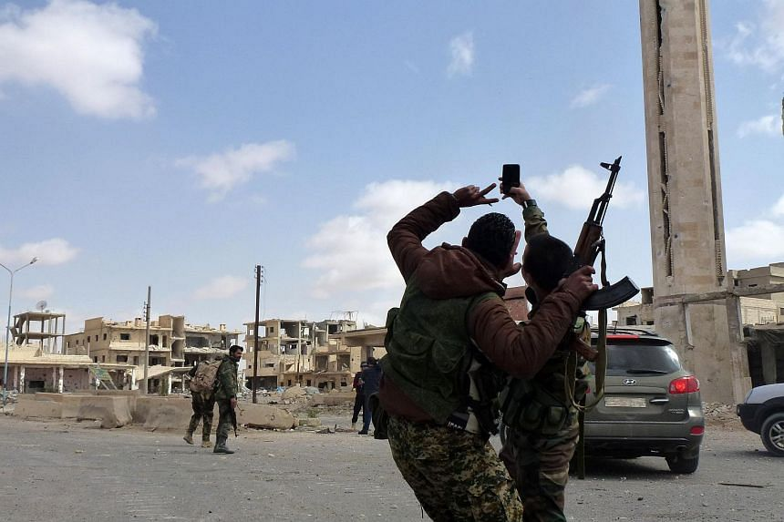 Syrian troops take a selfie in the damaged streets of the residential neighbourhoods in the modern town adjacent to Palmyra on March 27, 2016.