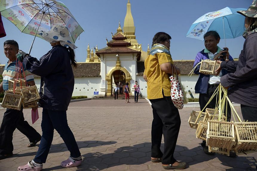 Tourists visit the Pha That Luang monument in Laos.