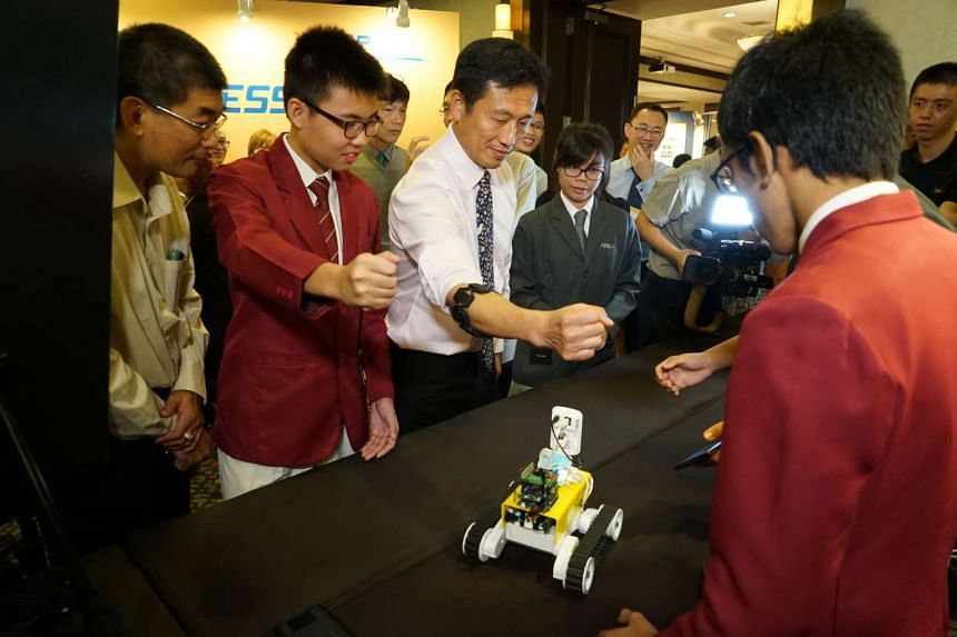 Senior Minister of State for Defence Ong Ye Kung trying out gesture control technology on an unmanned ground vehicle, designed by four students from Victoria School and the NUS High School of Mathematics and Science, on display at the YSDP Congress e