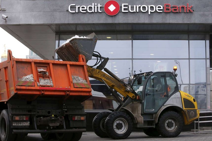 Workers remove snow outside a branch of the Credit Europe Bank in Moscow, Russia.