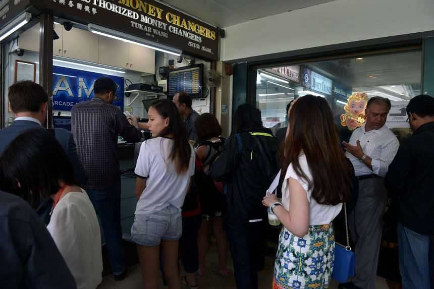 People queuing up at the money changer at the Arcade in Raffles Place on Feb 23, 2016.