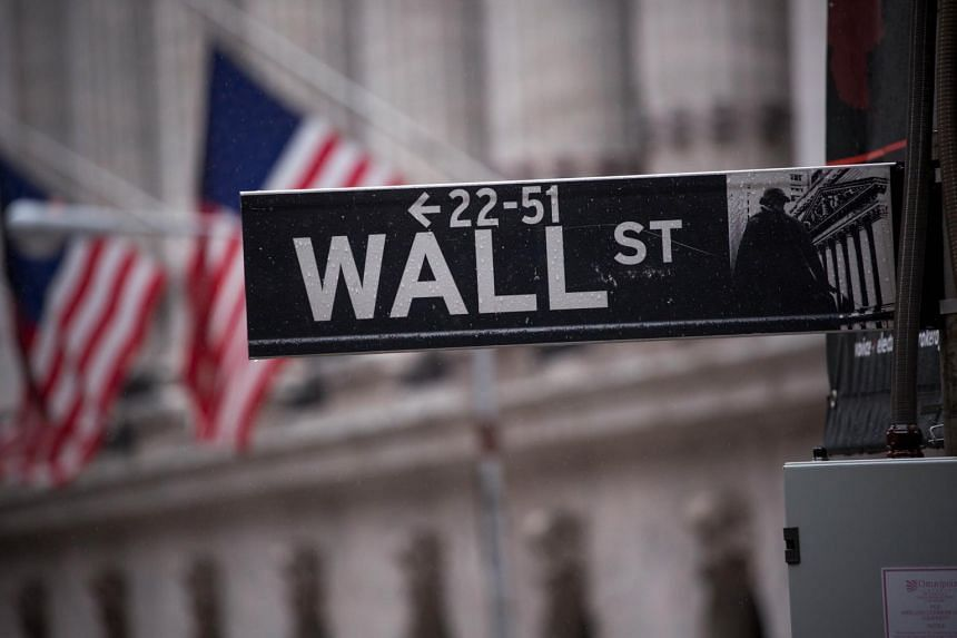 A Wall Street sign is seen in front of the New York Stock Exchange.